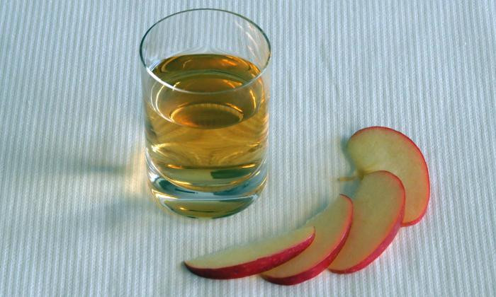 A glass of apple cider vinegar. Apple cider vinegar is made up of water, acetic acid, and several minerals. Apple cider vinegar is also used in naturopathy.