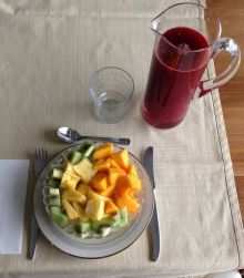 Snack for several people: mango, pineapple, kiwi and freshly squeezed blood orange juice.